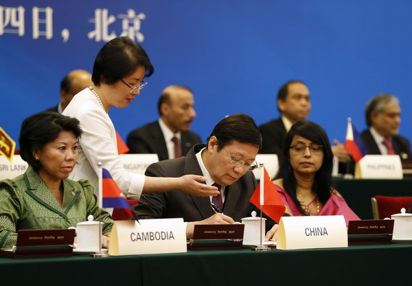 China's Finance Minister Lou Jiwei (C) signs a document, with the guests of the signing ceremony of the Asian Infrastructure Investment Bank at the Great Hall of the People in Beijing October 24, 2014. REUTERS/Takaki Yajima/Pool (CHINA - Tags: BUSINESS POLITICS)